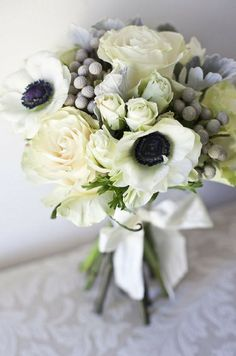 The perfect choice for a stylish city wedding, a simple yet elegant white bouquet with pops of black from gorgeous anemones, texture from garden and spray roses, and pretty silver hues from silver brunia berries and velvety sift  dusty milller leaves.