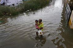 16.11 Ce vieille homme porte un enfant à travers les rues inondées de Chennai, en Inde.Photo: AP/Arun Sankar k