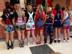 Adorned with glitter, bows and other leopard themed trinkets, senior girls pose on the Friday before a home game.