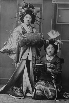 Two Young Beautiful Japanese Geishas accoutered in the ceremonial costumes and hairstyles of ancient Japan with Kimono, Combs and Obi