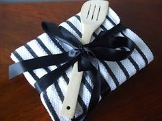 cookbook wrapped with a tea towel and adorned with a spoon... what a cute idea for a bridal shower or housewarming party!
