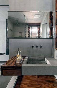 """Para ele: Previsto desde o início, o banheiro do marido recebeu cuba de limestone cinza. """"A pedra tem a mesma tonalidade do cimento, o que confere um aspecto homogêneo ao lugar"""", comenta o arquiteto."""