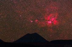 "Carina Nebula (NGC 3372) glowing pink above Chile's Chiliques volcano. (Image: Babak Tafreshi, TWAN) The nebula is about 7500 light years away in the southern hemisphere constellation Carina. The red color is light emitted from atoms of hydrogen gas interacting with UV radiation from massive young stars. The color is real, but your eyes wouldn't see it this way because they're not sensitive to color in dim light. Mona Evans, ""Nebulae"" http://www.bellaonline.com/articles/art43407.asp"