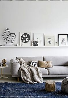 Art displayed on shelves, a softer overall palette.  Monochrome freehand artwork alongside geometric cushion, perfect balance with the addition of the vibrant blue rug.  Olive Living.