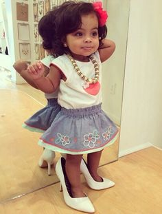 Beautiful baby girl playing dress up in Mom's heels & jewelry