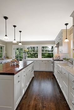 dark plank flooring, white cabinets, butcher block countertops, farm house sink, hanging pendant lights, windows, natural light