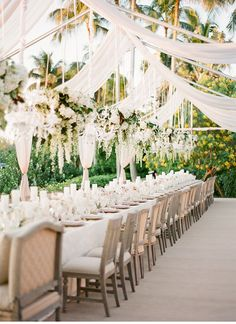 Play up a family-style seating arrangement by hanging rows of white floral chandeliers above your banquet tables.
