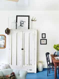 An antique armoire now acts as a makeshift closet, while a weathered writing desk and artwork by Holly's husband create a collected-over-time feel. A custom mix of bold paint on the floors—a custom Farrow & Ball blue—provides an unexpected pop of color. To brighten up the space, the beadboard ceiling and walls were painted a crisp white .