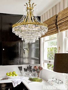 "A crystal chandelier and high-gloss kitchen cabinets painted Farrow & Ball's Pitch Black ""remind me of Paris apartments and grand French style,"" designer Tobi Tobin says."
