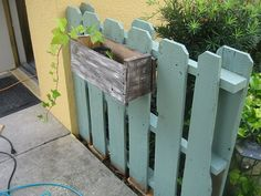A garden fence made out of pallets with flower boxes.