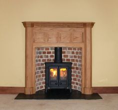 Bespoke oak mantel with curved reclaimed brick slip chamber, slate tiled hearth and Charnwood Island 1 multifuel stove. Fitted into a Goldsworthy property in Thorpe Bay Essex 2007