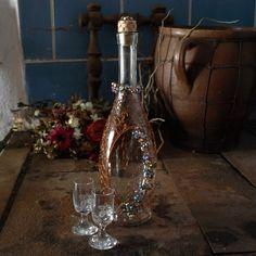 Drátovaná+láhev+s+květinovým+motivem+pro+dámu+Podarujte+drahou+polovičku+touto+elegantní+láhví.+Něžná+láhev+o+rozměrech+33+x+10+cm+(0,75+l)+je+jemně+opletenáměděným+drátkem,+ozdobená+květinovou+girlandou+z+broušených+korálků,+hrdlo+zdobí+korálkový+lem.+Součástí+láhve+je+i+odrátovaný+korek,+také+zdobený+korálky.+Zasílám+jako+křehké+zboží.