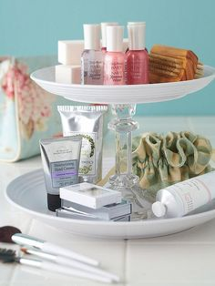 A DIY bathroom vanity organizer made from re-purposed plates and a candlestick.
