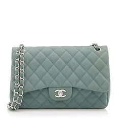 This iconic Chanel shoulder bag is made from quilted green suede caviar leather with silver-tone hardware. The must-have design features a signature CC turnlock, woven chain shoulder straps, and a green leather double-flap interior. Carry this style with the straps doubled-over or pulled through.