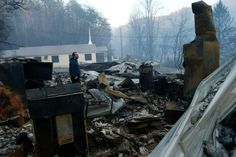 GATLINBURG, TN - NOVEMBER 29: Trevor Cates, walks through the smoldering remains of the fellowship hall of his church, the Banner Missionary Baptist Church as he inspects damage after a widfire November 29, 2016 in Gatlinburg, Tennessee. Thousands of people have been evacuated from the area and over 100 houses and businesses were damaged or destroyed. Drought conditions and high winds helped the fire spread through the foothills of the Great Smoky Mountains. (Photo by Brian Blanco/Getty…