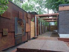 Cortenstahlwand als Akzent und Holz-Gartenzaun