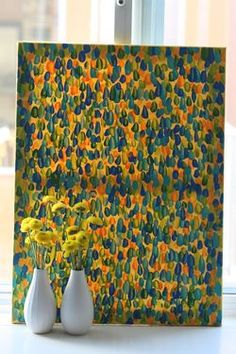 I had a large canvas and I painted it completely yellow. After it dried, I added finger painted swipes in five colors over and over until the canvas was full. Seriously so simple