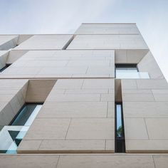 Angled window reveals and balconies interrupt the smooth limestone facades of this apartment building in Bucharest, Romania, by local architects ADNBA..