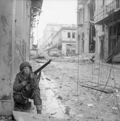A paratrooper from 5th (Scots) Parachute Battalion, 2nd Parachute Brigade, takes cover on a street corner in Athens during operations against members of ELAS, 18 December 1944.
