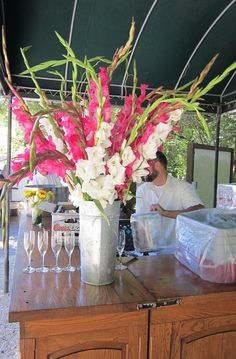 Showy gladiola arrangements in fushia, tangerine and white for welcome table and bars at wine reception / use heavy glass vase (not one shown) / reasonably priced