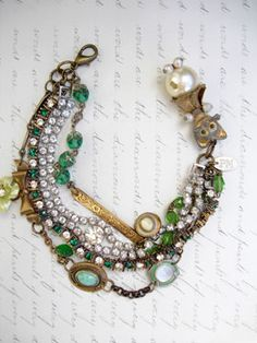 """Here Kitty Kitty Kitty - 4 Strands """"Complicated"""" Repurposed Bracelet in Greens with Cat This 4 strand bracelet has 2 vintage, rhinestone bracelets. Both are prong set. One is clear with 2 strands (which, technically, makes this a 5 strand bracelet) and a round center stone. The other is high set stones alternating green with clear. Strand number 3 is a made up of 4 different chains and interrupted by a repurposed bow pin from which I hung a vintage pale green with rhinestones..."""