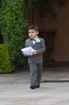 Ring bearer wearing a grey suit with a dark purple bow tie, carring the rings down the aisle on a white pillow | Studio World Photography | villasiena.cc