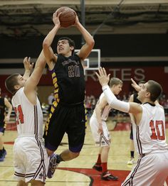 New Berlin Eisenhower's Jordan Canady goes up for a shot against Pewaukee's Seth Bickett (left) and Alex Clement in the first half at Pewaukee on Jan. 15. Eisenhower won the game, 77-49.