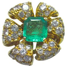 Fabulous 1960s Emerald & Diamond Flower Ring in 18kt Gold Crafted of 18kt gold this stunning flower is set with approx 7.00 carats of diamonds surrounding an apporx 4.00 carat natural colombian emerald.