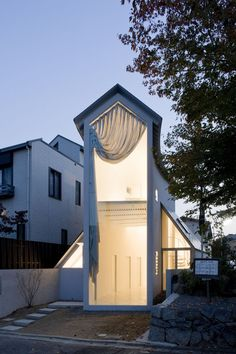 Japan. Facing the road, the tall double-height window at the end of this narrow home is artfully draped by a curtain.