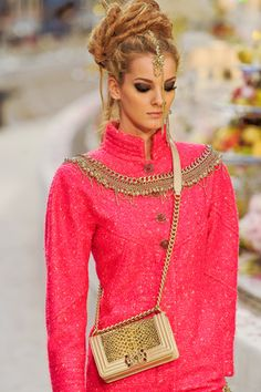 From Chanel 2012 Pre-Autumn. I LOVE this because it's a bright rosey coral pink, which is one of my favorite colors (working on a bracelet with this color right now). I also love the ethnic influence in the styling, like traditional Indian adornments, clearly a match-up to the same influence on the trim across the chest. Of course, the Chanel hand bag is a staple item in any runway look, and this one has a box shape and that same ethnic look to it. This is really special and beautiful.