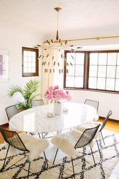 A modern dining room with a marble table and unique chandelier