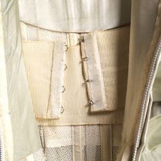 DJ6: This is a Balmain evening dress from 1958 with a built-in foundation piece. When I worked a bridal stores I remember that all bridal gowns had this as well. It helps support the bust as the gown weight weighs her down.