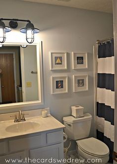 Bathroom Makeover. The the color of the walls with the navy stripes curtain and light fixture