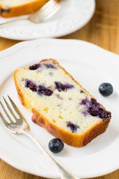 A portrait photo of a slice of blueberry lemon yogurt cake loaf on a white plate with two fresh blueberries and a small silver fork.