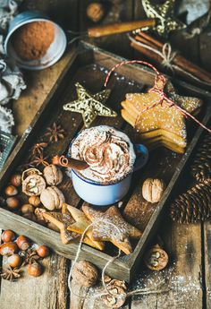 Mug of hot chocolate gingerbread cookies nuts in wooden tray by 2enroute