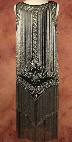 1920's Beaded Flapper Dress. Silver and iridescent sequined fronds and steel beaded vines expertly frame the shoulders and neckline and captivate as they flow through the torso. The bead and the sequin decor makes this dress an art deco masterpiece. Back