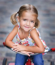 Cute little girl on a tricycle in pony tails.