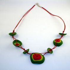 Collar de cazuelitas en dos tonos de verde y en rojo a juego con el cordón.   Desenfadado y muy actual. Combina muy bien con un estilo urbano, casual y juvenil.
