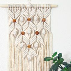 This macrame boho wall hanging is soft and has a simple modern design that can complement a variety of decor styles. I designed and hand knotted this piece using cotton twine and hand-dyed wood beads. Natural variations in the cotton twine color may occur and range from white to