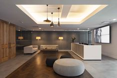 A modern but warm office reception design by Office AO Architecture, a full service architecture firm based in New York City. The photo shows the reception area for a 50,000 square foot office we recently design.   Herringbone wood floor inlayed into Florida Tile. Custom wood doors in full height frameless glass storefront . Tom Dixon Lights and ABC Home furniture, contrast the custom designed reception desk.