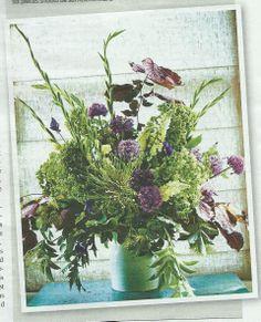 Flower arrangement with alliums, gladioli, lupins, hazel, euphorbias, clematis and elderflowers.