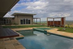 Byron Bay Area hilltop Garden with reclaimed bridge timbers and Corten rusted Steel Pergolas and pool fence and seating