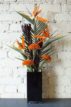 A simple tropical flower vases in autumn shades, including orange celosia, leucadendron and strelitzia. The autumn colours have been very popular this week in the shop! #reidsflorists #autumnflowers #corporateflowers