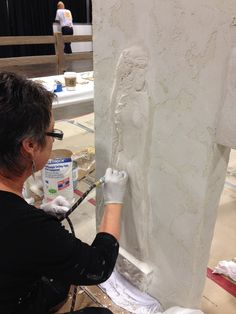 Ellie Ellis, CMS. Carving a cement relief at the Concrete Decor Show where she won first place.