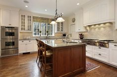 White country cabinet kitchen with wood island and wood flooring