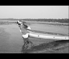 Fishermen carrying their boat to the sea at Gorai Beach, South Mumbai.