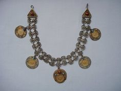 Woman's necklace or head ornament in gilded metal; a double chain formed of pairs of filigree rosettes with an applied lozenge at the join, ending in triangular filigree clasps with hook and eye fittings, each set with a red glass stone and a further applied lozenge. From the lower row of rosettes are suspended five coins of Peter II of Yugoslavia (1934-45) all dated 1938: two 50 para, two 1 dinar and one 2 dinar piece, each with Kraljevina Jugoslavija (Kingdom of Yugoslavia) in cyrillic on…
