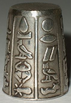 Silver thimble from Egypt. Embossed with a wide variety of Egyptian motifs / hieroglyphics arranged vertically in panels around the thimble body. Fine diamond waffle pattern top. Hand made in two parts - body and crown. The thimble is marked with the Egyptian Cairo office hallmark for 800 silver in one of the panels.