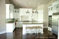 Gorgeous white kitchen - love the two pendant lights and the top glass cabinets eclecticallyvintage.com