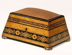 """Antique 1800-1840 British Box at the Victoria and Albert Museum, London - From the curators' comments: """"This small box is decorated with veneered bands of Tunbridgeware. This consists of patterns made up of tiny cubes of wood. The cubes were made from bundles of blocks that were finely cut across the grain. A pincushion covers the top, so the box was probably used to store sewing accessories. It was made in Tunbridge Wells in Kent."""""""